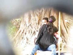 College girl rides her boyfriend by the tree